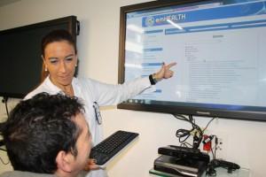 Erika Otxoa muestra la plataforma EM Health a un paciente con EM